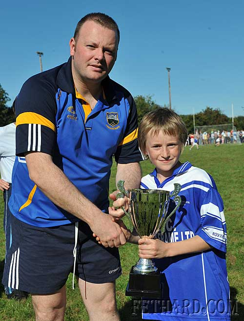Tipperary and Fethard goalie Paul Fitzgerald presenting David Murphy, captain of Rockwell Rover, with Cup following his team's win in the Inter-Club Football Blitz at Fethard Community Field Day.