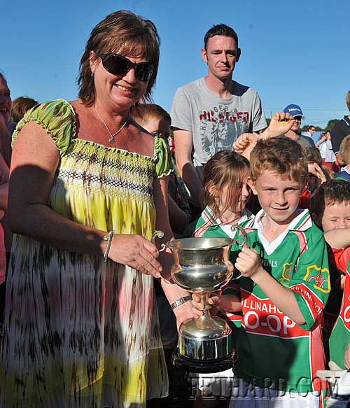 Ann Fleming presenting the Danaher Cup to Éanna Ryan, captain of Mullinahone Under-8 football team. Winners of the Under-8 football blitz at Fethard Community Field Day.