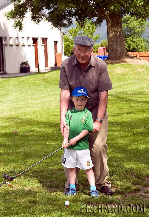 Retired teacher Paddy Broderick giving his grandson Dan a few lessons in his new sport at Slievenamon Golf Club
