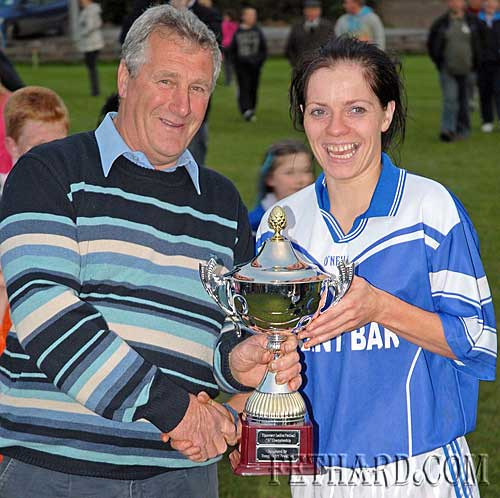 The chairman of the Ladies Football County Board, Enda McDonald, hands over the cup to Fethard's captain after their tiumph over Emly in the Junior County Final.