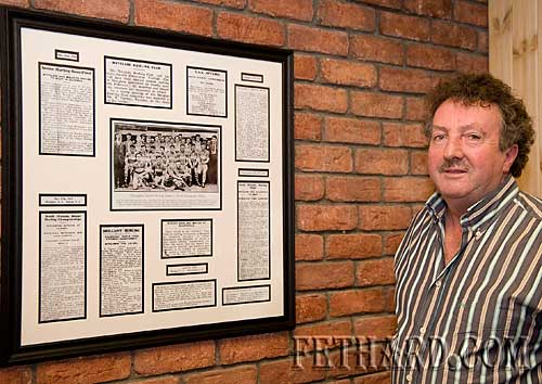 Matty Tynan photographed with framed clips of match previews and reports taken from the Nationalist of 1934.