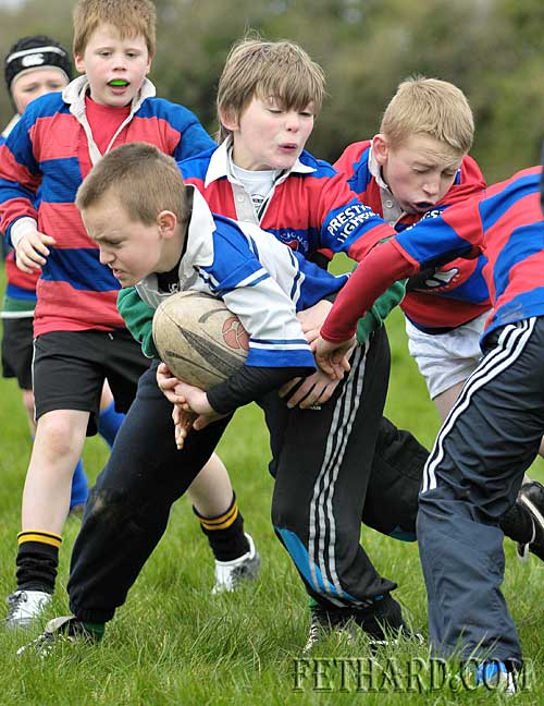 Fethard's Jack Dolan holds the ball despite close attention from several Carrick players in their under-9 match played in Fethard last weekend