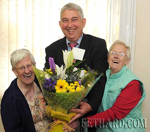 "Paul Davey, Manager of Fethard Credit Union, presenting flowers to twins, Joan and Eileen Gleeson, who were first customers at the office on Friday 4th June after the  the ""transfer of engagements"" by Fethard and District Credit Union to Clonmel Credit Union.  Both Board of Directors had previously met and approved the transfer on the 1st June."