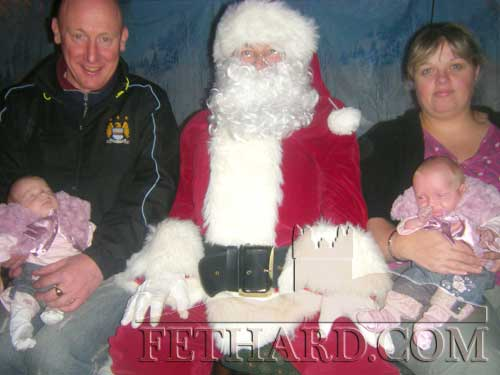Twins visit Santa — John Kelly and Urusla Bradshaw photographed with twins, Caolinn and Aislinn, at Lonergan's 'Winter Wonderland' wher Santa visited last Sunday.