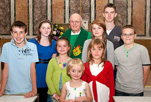 Fr. Joe Walsh OSA photographed with L to R: Kevin Hickey, Kate Guinan, Ava Hickey, Sari Miller, Katie Miller (red), Ellen Walsh, Daniel Guinan and James Walsh.
