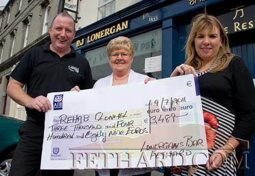 Proprietors of Lonergan's Bar Fethard presenting a cheque for €3,489, proceeds of their recent X-Factor 2011 competition, to Mary B. O'Donohoe, representing Re-Hab, Clonmel. The bar will hold another fundraising event for Re-Hab at Halloween. L to R: John Carroll, Mary B. O'Donohoe and Roseanne Carroll.