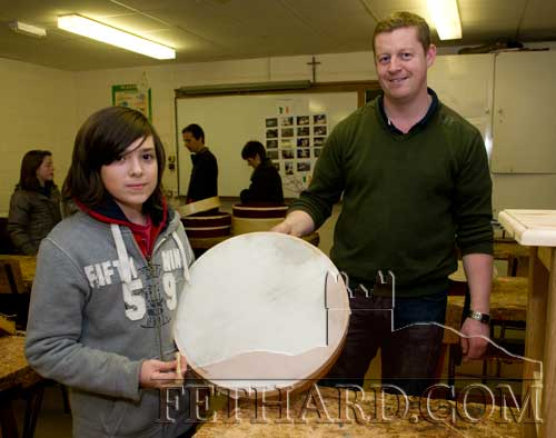 Teacher John Cummins displaying a bodhrán made in the woodworking room to Dylan