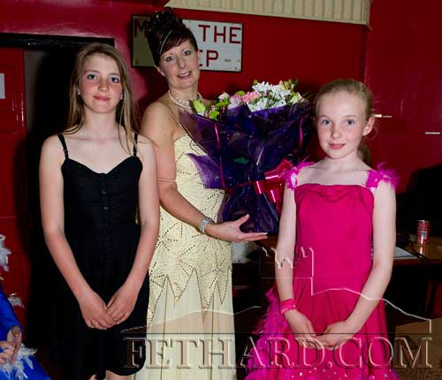 Courtney Walsh (left) and Emma Jayne Burke presenting competition organiser, Marina Mullins, with a bouquet of flowers.