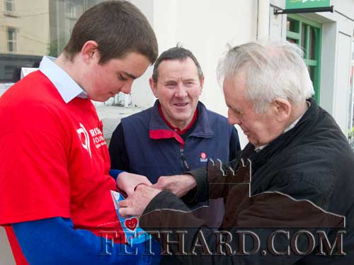 Joe Keane and Gussy Breen buying their 'Happy Heart' badges from TY student James Maher