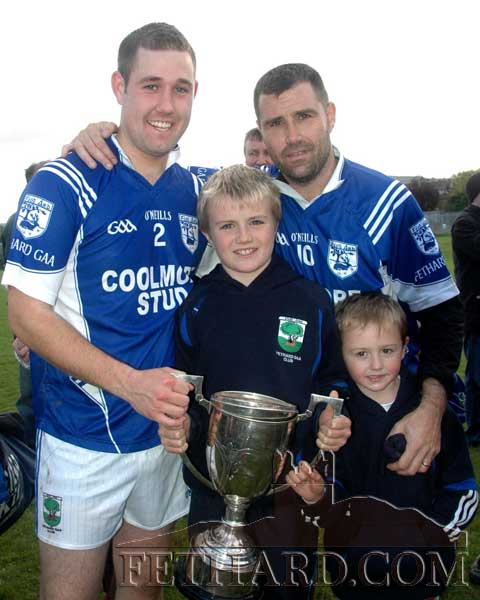 Fethard's Peter Gough and his uncle-in-law Eugene Walsh proud to show the Junior B Football trophy to Eugene's two sons, Ryan and Charlie.