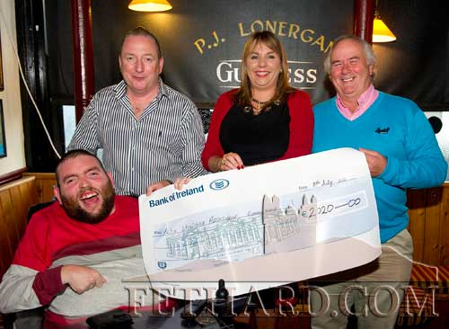 John and Roseanne Carroll, proprietors Lonergan's Bar, presenting a cheque for €2,020, proceeds of the recent 'Music Extravaganza', to John Ryan and Jack Kenny, representing the Tipperary Branch of the Irish Wheelchair Association.