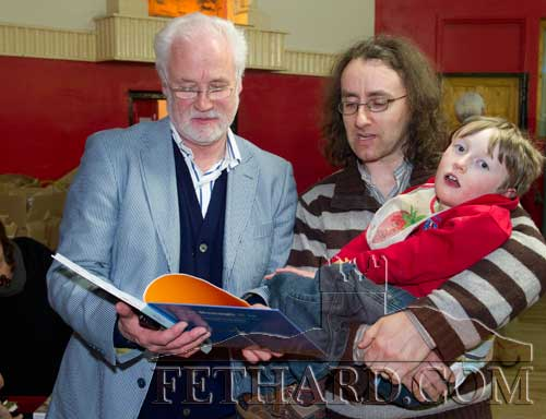 Photographed at the Tipperariana Book Fair in Fethard Ballroom are L to R: Pádraig Ó Flannabhra showing his book, 'It is Nenagh It is' to Barry O'Reilly and his son Fionn.