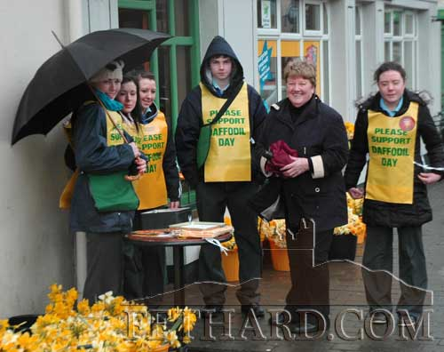 Local Daffodil Day organiser, Ann Connolly, photographed with helpers outside Fethard Post Office on a wet and windy Daffodil Day.