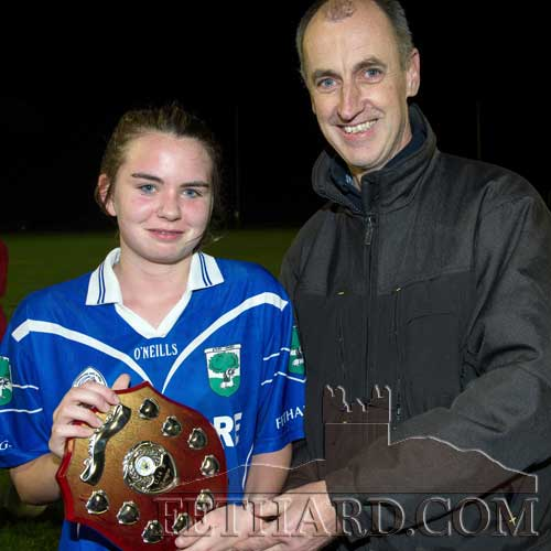 Laura Stocksborough, captain of the Under 14 Ladies team, is presented with the trophy by Chairman of the Tipperary LGFA, Tommy Campbell, following Fethard's team win in the County League final.