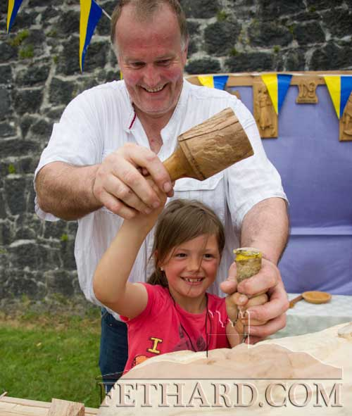 David Gorey giving Jessica Stokes a few tips on woodcarving at Fethard Medieval Festival