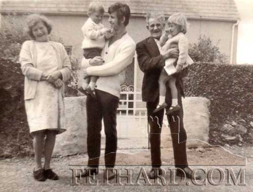 This photograph was shared by Kath Duffy, Birstall, UK, who is a daughter of Tom Leahy, formerly from the Kilnockin Road. The photograph is L to R: Bridie Leahy, Tom Leahy holding his son Chris Leahy, and Gerry Leahy holding his granddaughter Kath Leahy outside their house on Kilkockin Road (around 1970).