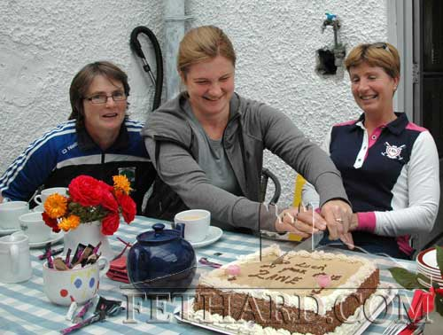 Zane Zorina (centre) cutting a cake supplied by her friends in Fethard Athletic Club at a farewell coffee morning to mark her departure from Fethard. Also included are Noreen Sheehy (left) and Ginny Hutton.
