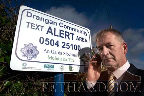 Mr James O'Neill, Community Alert Development Officer with Muintir na Tire, photographed with one of the Text Alert signs in neighbouring Drangan parish.