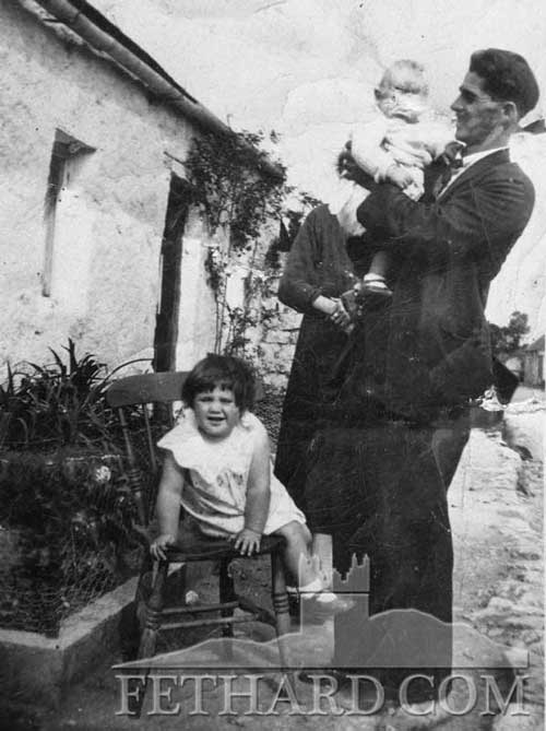 Harry Sayers holding John (Buddy) Sayers with Catherine Sayers (John's daughter) on chair. Taken outside old home in the Valley. John was on holiday from America. Catherine lives USA.