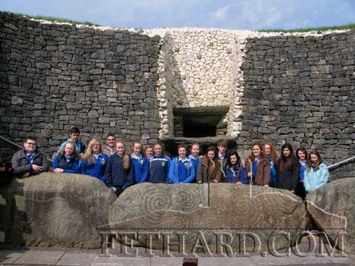 Patrician Presentation Secondary School students photographed in front of the famous entrance stone, one of 97 stones that run around the base of the mound at Newgrange. The 'roof box' over the entrance can also be seen overhead in the centre background.