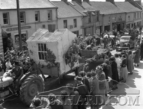 Fethard Carnival c.1960s passing outside the Parish Church where it is interesting to see tha many open businesses across the road from L to R: Percy Dillon's Chemist Shop, Lil McCarthy's Sweet Shop, Kay Fahy's Ladies Hairdressing, Fethard Bakery, O'Connell's Furniture and Electrical Shop, Jack O'Shea's 'While U Wait' and another shop premises but can't make out the name.