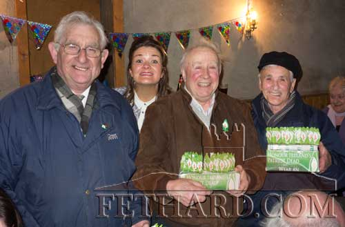 Selling Easter Lilies in The Thatch Pub last weekend were L to R: Mícheál De Faoite, Marcus Fogarty and Tadhg Ó hÍnse with an enthusiastic customer behind wanting to get in the picture.