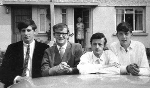 "The late Eamon Maher photographed with his friends outside Conor Lanigan's house, Árd Mhuire, Thurles, in 1965. L to R: Bill Maher (Main Street), Michael Maher, Eamon Maher and Conor Lanigan.  Michael Maher has finally solved the identity of the mystery man in the photo after receiving a phone call from an old acquaintance who saw the photo on the internet and opened the conversation with the words, ""God didn't we all look well in that photo!""  His name is Conor Lanigan from Árd Mhuire in Thurles and the photo was taken in 1965 by the late Liam Whyte (Main Street) outside Conor's house in Thurles with his mother in the background. The group were more than likely heading off to a dance in the Premier Ballroom later that evening.  Michael's memory was jogged by the fact that Stephen (Fitzgerald) rang him to say that he had met Maureen Whyte while out walking last week and informed him that she had also found the photo while sorting out some of Liam's possessions. It's amazing how little reminders can unleash many other memories as Michael had never seen the photograph before and wasn't sure where it was taken."