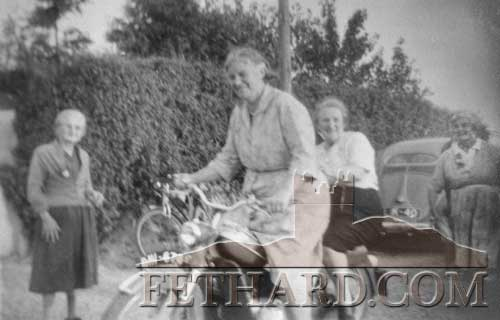 Nellie Fitzgerald photographed on Gus Murray's motorbike with Kitty Flynn on the back, looking on is May Wall (left) and Nora Burke (right). Taken 15th September 1959.