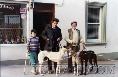 L to R: Boy, Michael Keane and Timmy O'Riordan holding their greyhounds outside Flynn's shop