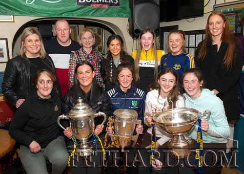 Members of St. Rita's Camogie Club who won the overall Team of the Year award for 2019. Back L to R: Mary O'Mahoney, Miceál Spillane, Sandra Spillane, Leah Coen, Heather Spillane, Carrie Davey,  special guest Aishling Moloney. Front L to R: Annette Connolly, Annette Connolly, Mary O'Mahoney, Sandra Spillane. Front L to R: Nell Spillane, Katie Ryan holding the Thomas Nolan Cup (U20 Hurling), Nell Spillane holding the Liam McCarthy Cup (Senior Hurling), Allison Connolly and Lucy Spillane holding the Mary Quinn Cup (Ladies Intermediate Football).