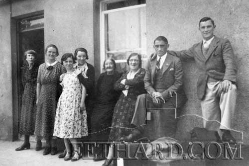 Emigration as many will remember – these two lads with bags packed, are photographed with neighbours before leaving The Green for England in the early 1940s. L to R: Alice Carey, Katie (Kenny) O'Brien, Ursula O'Brien, Mary O'Brien, Bridget and Maggie Carey, Jimmy Walsh and Mattie Higgins.