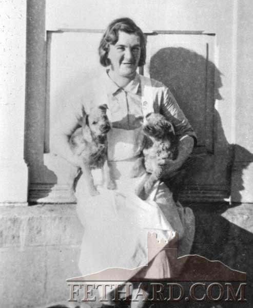 Mrs Sarah Cashman, The Back Green, Fethard, holding two puppies outside the back door of Kiltinan Castle, where she worked at that time.