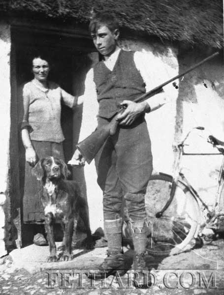 Any information on this photograph would be great . . . Young boy with a gun watched by woman standing in doorway with hunting dog outside thatched cottage?